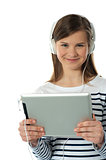 Beautiful girl listening to music via wireless tablet