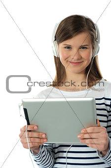 Beautiful girl listening to music via wireless tablet