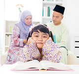 Malay girl reading book.