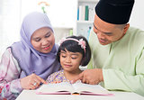 Malay Muslim family reading a book.