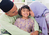 Muslim parents kissing child.