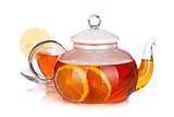 Glass teapot and cup of black tea with lemon
