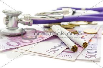 Cigarettes and stethoscope on Euro money