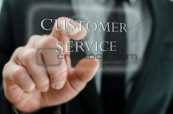 Business man pointing at Customer service icon on a virtual scre