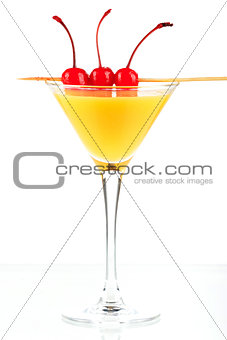 Alcohol cocktail with orange juice and three maraschino
