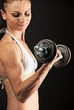 Muscular young woman lifting a dumbbell