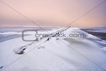 old breakwater in North sea under snow