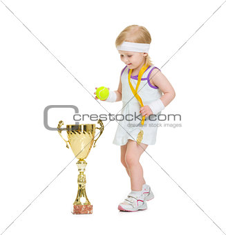 Baby in tennis clothes with medal and goblet