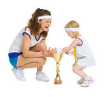 Mother and baby in tennis clothes with medal and goblet