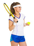 Smiling female tennis player with racket and ball looking on cop