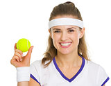 Happy female tennis player showing tennis ball