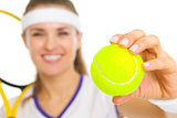 Closeup on tennis ball in hand of female tennis player