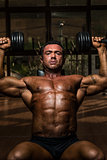 male bodybuilder doing shoulder press whit dumbbell