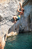 Deep water soloing, female rock climber on cliff