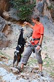 Climber feeding a goat at a cliff