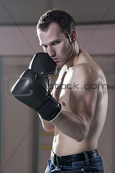 Waist-up of male boxer in gym