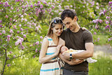 Young couple with newborn son outdoors