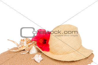 straw hat ans seashells on sand