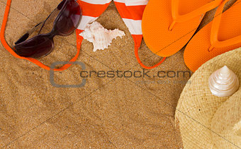 orange sandals  and sunbathing accessories at sand