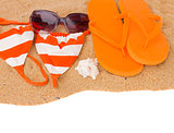orange sandals and swimming siut on sand