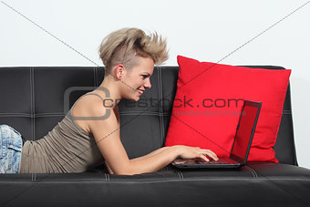 Fashion woman browsing internet in a laptop at home