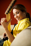 woman playing and training with electric guitar at home