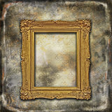 Gold coated wooden baroque empty frame on faded grunge texture