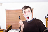 Shocked male with shaving cream and razor blade