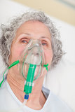 Elderly woman with an oxygen mask in a hospital