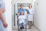 Smiling nurse assisting senior woman sitting in a wheelchair