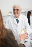 Smiling male pharmacist pointing at a box of pills