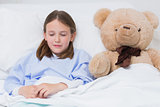 Child sleeping with a teddy bear while lying in a bed