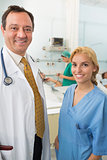 Smiling doctor and smiling nurse talking in a hospital ward