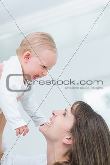 Mother holding her child while smiling