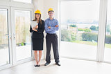 Estate agent and client wearing hardhats
