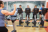 Enthusiastic woman teaching spinning class