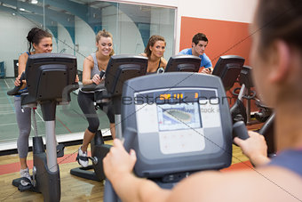 Smiling group taking spinning class