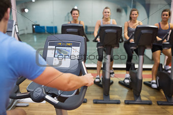 Man teaches spinning class to happy women