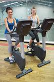 Two happy women on exercise bikes