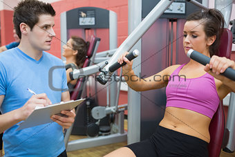 Trainer noting progress of woman using weights machine