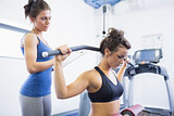 Woman using weights machine with female trainer