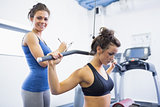 Smiling trainer with woman using weights machine