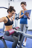 Female trainer taking notes on client on weights machine
