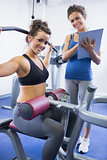 Happy female trainer and client on weights machine