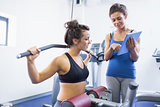 Trainer with woman on weights machine