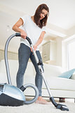 Woman cleaning the carpet in the living room