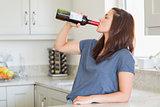 Woman drinking a bottle of wine alone