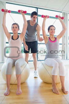 Trainer teaching class on exercise ball