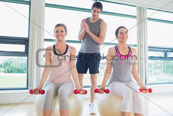 Trainer teaching his class lifting weights
