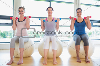 Women lifting weights on exercise balls